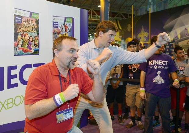 Sports on Earth reporter Mike Tanier (left) and New York Giants quarterback Eli Manning participate in a Xbox360 Kinect boxing game at the Super Bowl XLVII Experience at the Ernest N. Morial Convention Center.