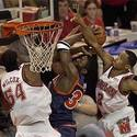 Terps Chris Wilcox (54) and Juan Dixon (3) try to block Cavaliers Jason Clark (34)