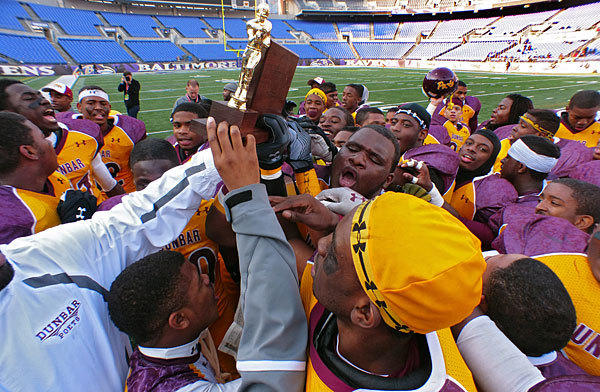 Players and coaches for No. 6 Dunbar celebrate after the Poets' 39-0 victory over New Town in the Class 1A football state championship at M&T Bank Stadium.