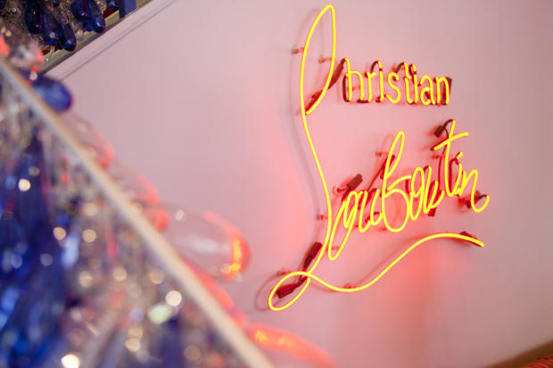 Louboutin's name is lit up in neon inside the West Hollywood store, where the famous designer of much coveted, red-soled creations gave out his autograph on Wednesday.