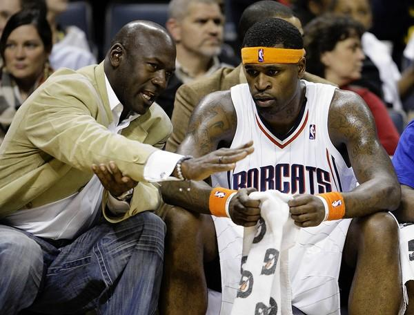 Bobcats managing partner Michael Jordan talks with Stephen Jackson during the first half of a game.