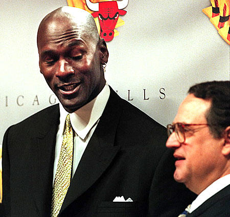 Michael Jordan gives a quizzical look to Bulls chairman Jerry Reinsdorf during the announcement of Jordan's second retirement.