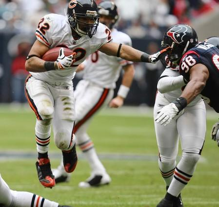 Matt Forte carries the ball as he pushes Houston's Anthony Weave away during the first quarter.