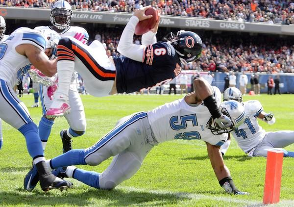 Jay Cutler dives over Detroit's Julian Peterson for a touchdown in the first quarter.
