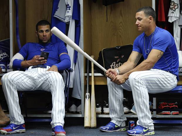 Javier Baez of the Mesa Solar Sox holds a bat as teammate Rubi Silva watches in the the locker room before an Arizona Fall League game against the Peoria Javelinas at Hohokam Stadium.