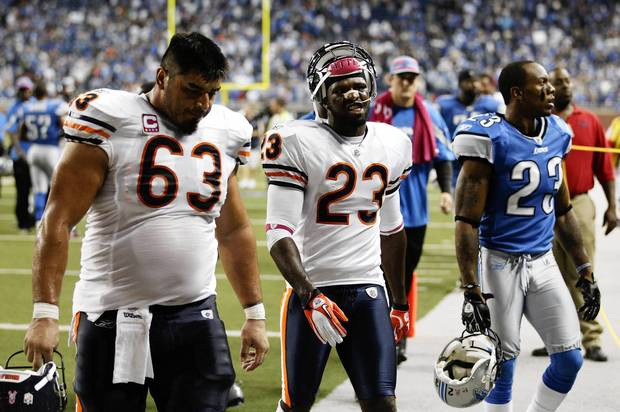 Roberto Garza and Devin Hester leave the field after their loss to the Lions at Ford Field.