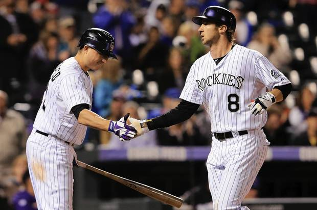 Rockies' Charlie Blackmon is welcomed home by Jordan Pacheco after his solo homer off of Cubs starter Jason Berken in the third inning.