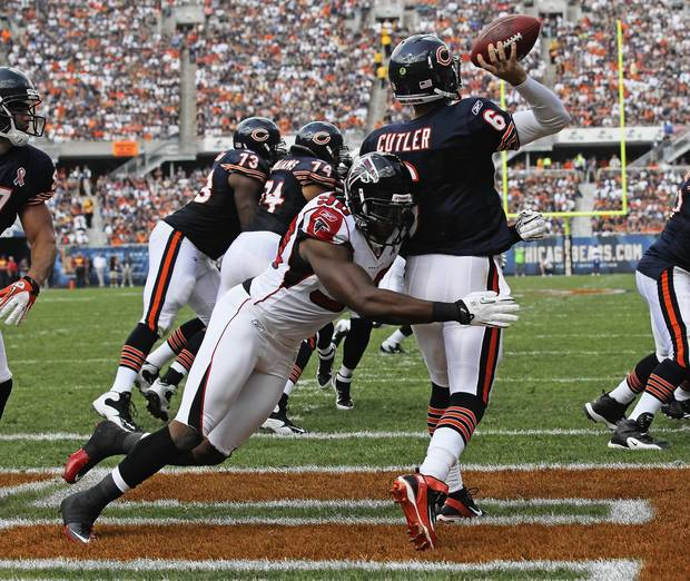 Jay Cutler is hit while throwing a pass from the end zone by Atlanta's Lawrence Sidbury.