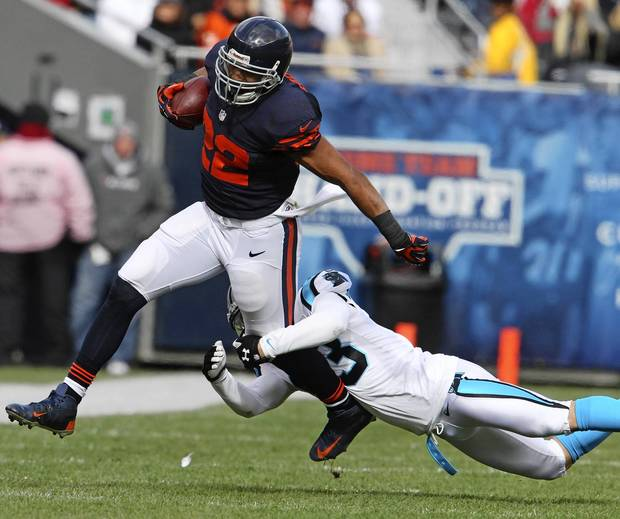 Matt Forte gains eight yards before a tackle by the Panthers' Haruki Nakamura in the first quarter.