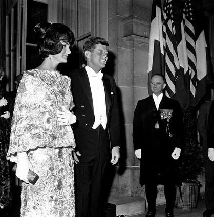 First Lady Jacqueline Kennedy wears an Oleg Cassini confection of pink and white straw lace as she and President Kennedy stand outside the Quai D'Orsay in Paris in 1961.