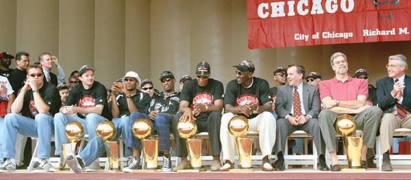 The Bulls celebrate their sixth NBA title during a rally in Grant Park. From left; Luc Longley, Tony Kukoc, Ron Harper, Dennis Rodman, Scottie Pippen, Michael Jordan, Mayor Richard M. Daley, coach Phil Jackson and Gov. Jim Edgar.