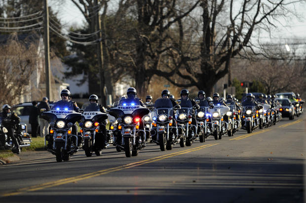 A police motorcycle escort leads the funeral procession to the Lordship Community Church in Stratford Wednesday morning for the funeral service for Victoria Soto, one of the teachers killed in Friday's massacre at Sandy Hook Elementary School in Newtown.