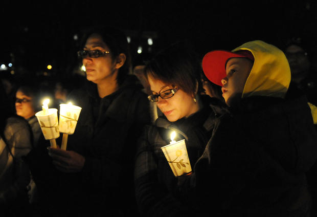 Virgin Rodriguez, second from right, holds her son, Elias, 5, during a candlelight vigil at Hartford's Bushnell Park Friday night in memory and prayer for the students and teachers who died at Sandy Hook Elementary School in Newtown earlier in the day. More than 100 people stood in the cold near the Bushnell Park Carousel.
