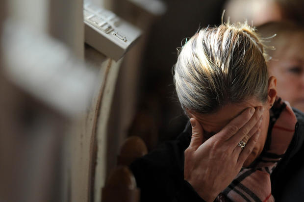 A mourner takes part in a healing service at St. John's Episcopal Church Saturday afternoon. The service was held to offer comfort and prayer to those coping with the tragic events at Sandy Hook School Friday.
