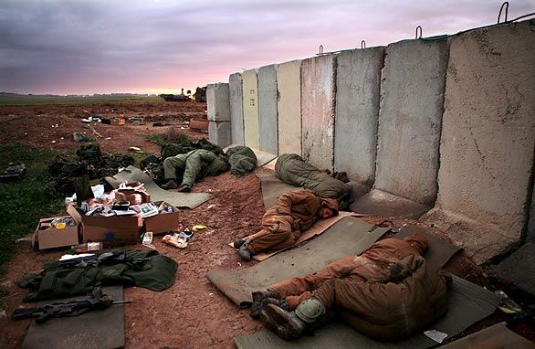 Israeli infantry soldiers catch some sleep at a blast barrier just inside the Israeli  border with the  Gaza  Strip.<br> <br> <b>Complete Coverage:</b><br>