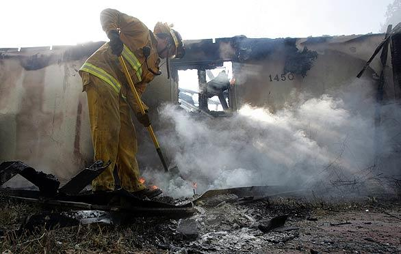 A Los Angeles City firefighter puts out a hot spot on the north end of Tunnel Road near Santa Barbara.