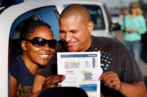 "Michael Jackson fans Shaneese and Bob Lewis, of Palm Springs, show off the vouchers for tickets to the Jackson memorial that  they won in an online lottery. The couple were among those lining up outside  Dodger Stadium to get their tickets and wristbands to  the Tuesday event.  ""I feel very lucky,"" said Bob Lewis, who won the tickets.  ""I learned to dance watching Michael Jackson."""