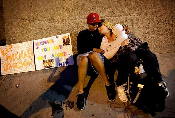 From left, Michelle Ushe and Cassandra Anderson from Orange County relax on Olympic Boulevard in the early morning hours as they wait for the Michael Jackson public memorial to start.