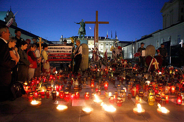 People pray and mourn in front of the wooden cross set outside Poland's presidential palace after the April, 10 2010 Tu-154m plane crash that killed 96 people, including the late Polish President Lech Kaczynski.<br> <br> The cross will be moved later Tuesday to the nearby Church of St. Anna, a joint decision by President Bronislaw Komorowski and the Warsaw Diocese. The memorial cross has become a divisive issue in Poland and many protesters are blocking authorities from moving the cross.