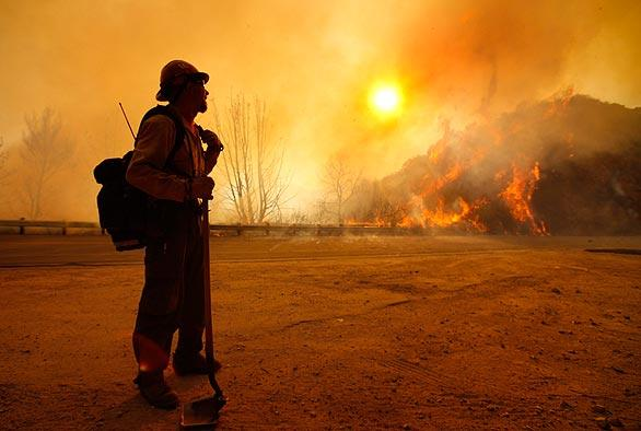 Firefighter Scott Allen glances across  Angeles Crest Highway as canyon winds whip up flames at sunrise.