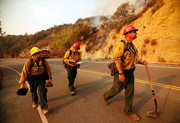 Forest service fire Capt. Mike Scott, right, with firefighters Joe Valencia, left, and Armando Pina walk along Angeles Crest Highway above La Ca?ada Friday morning to assess the Station fire. Friday will be hot again, with temperatures hovering near 100 degrees.