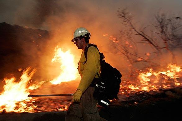 A firefighter walks along a control burn applied in the neighborhood of Pinecrest in La Crescenta. The fire was set to protect homes from the Station fire, which has charred 122,000 acres.