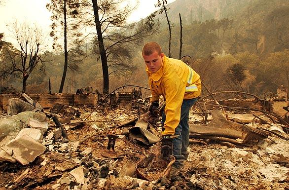 Travis Riner, 25, tries to salvage whatever he can from the charred remains of the home where he had lived for eight years on the 3000 block of Stonyvale Road at Vogel Flat in Tujunga.