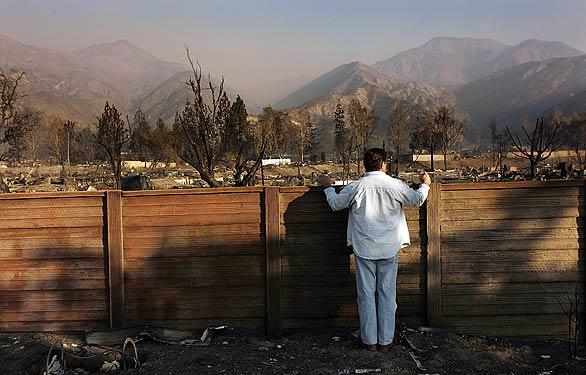 "Carl Cortez of Lake Arrowhead looks over the wall enclosing Oakridge Mobile Home Park  on Monday morning. His mother's and his sister's mobile homes were destroyed when fire swept through the Sylmar mobile home park. Cortez said, ""The fire must have been unbelievably hot to melt steel like it did."""
