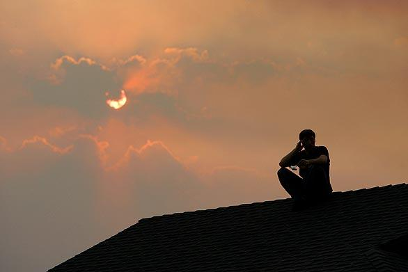 A  resident sits on his roof to watch the Station fire burn in a canyon near homes off Boston Avenue in La Crescenta.