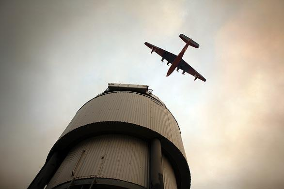 A Martin Mars Super Scooper flies over one of the telescopes atop Mt. Wilson, moments before dropping 7,200 gallons of water to keep flames away from the Mt. Wilson Observatory and radio towers Tuesday.