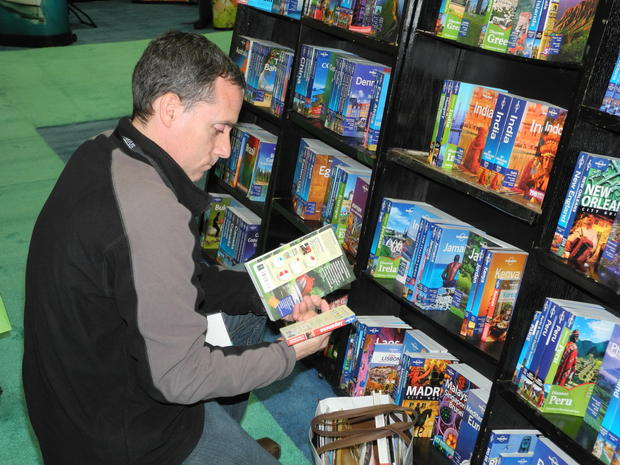 A browser checks out books from Distant Lands, which has a booth at the L.A. Times Travel show.