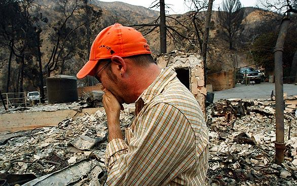 A man who identified himself only as Adi is overcome with emotion as he surveys the charred ruins of his home Wednesday in the 2400 block of Stonyvale Road in Tujunga.