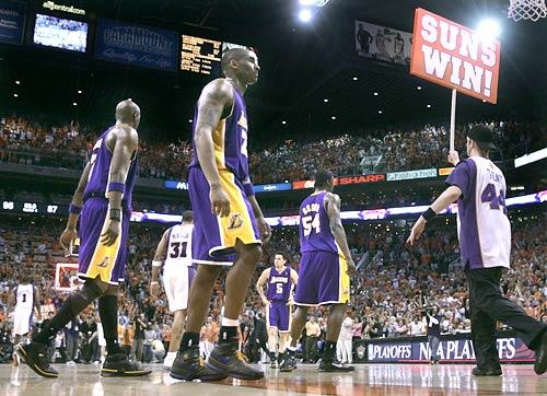 Kobe Bryant and his Lakers teammates walk off the court after they lost, 95-87, to the Phoenix Suns in Game 1 of the first round of the NBA playoffs at US Airways Center in Phoenix. The Suns went on to win the series, 4-1.