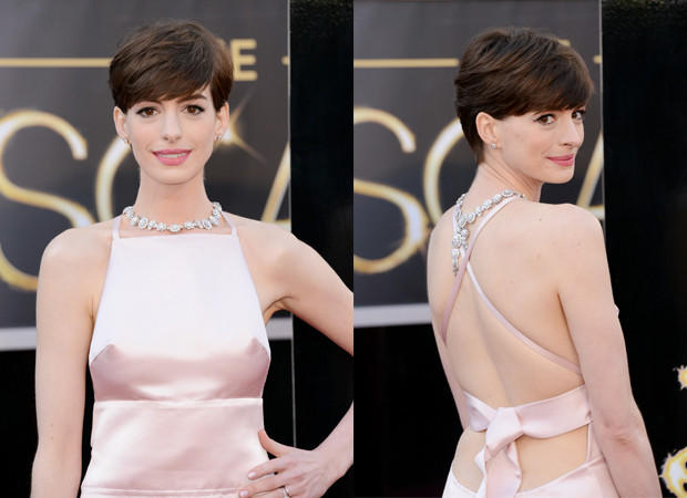Actress Anne Hathaway wears diamond stud earrings along with a necklace that drapes down her back.