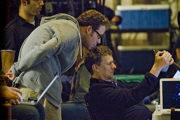 "Director Michel Gondry holds up his laptop for Seth Rogen to view in an off-set ""video village"" area of a Sony soundstage."