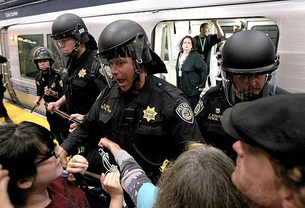 Bay Area Rapid Transit  police push back demonstrators who are trying to keep a train from leaving the Civic Center station  in San Francisco.<br>