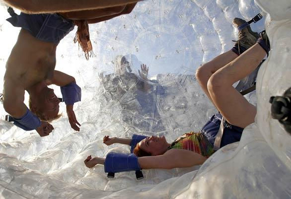 "People get inside an interactive art piece made of a large inflatable rolling ball created by ""Dr. Dave"" at Burning Man 2008."