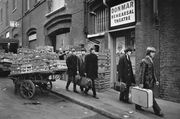 The Rolling Stones file down a Covent Garden back street in 1963, past the Donmar Rehearsal Theatre and a cart of fruit and vegetables. Charlie Watts, left, Keith Richards, Mick Jagger, Bill Wyman and Brian Jones.