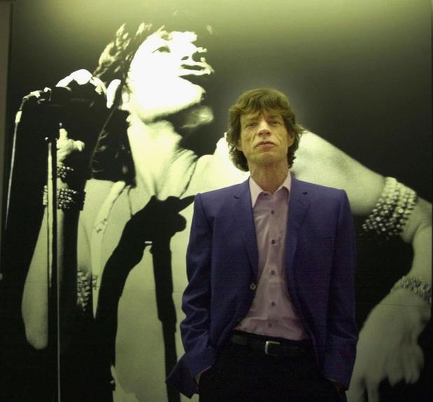 Mick Jagger stands in front of a concert photograph of the himself situated in the new music studio at Dartford Grammar school on March 30, 2000, in Dartford, England.