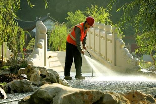 An artisan sprays clean the rustic stones that have been artfully set into place near the Jade Ribbon Bridge.