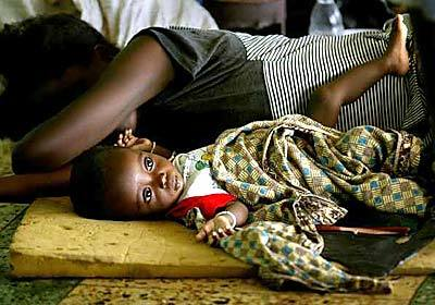 Ju Sieno, 7 months, lies beside his mother Hawa David,  19, at the National Stadium of Monrovia, Liberia, where thousands have come for safely from the recent fighting.