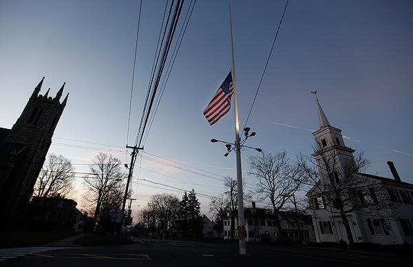 A flag flies at half-staff as dawn breaks Saturday in Newtown.