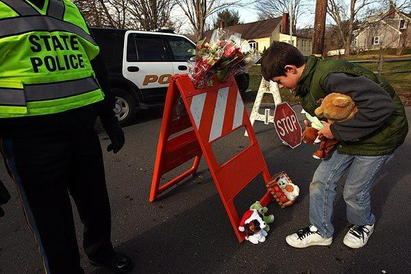Noah Iott, 10, leaves stuffed animals at a police barricade — the closest he could get to Sandy Hook Elementary School on Saturday — in memory of the people killed there the day before. Noah lives in the nearby town of Seymour.
