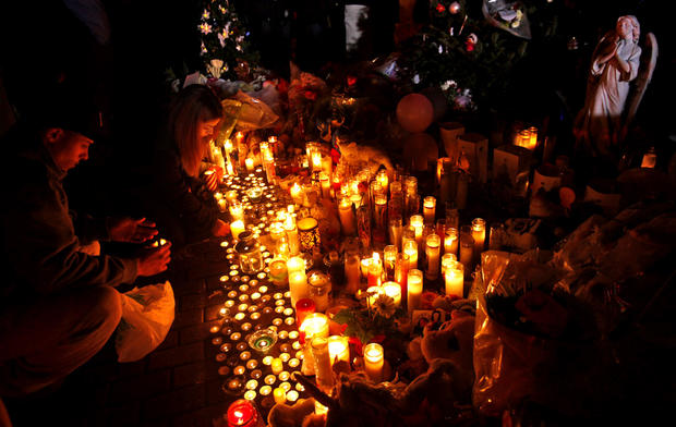 People continue to light candles at a makeshift memorial to those that lost their lives in the Sandy Hook Elementary School shooting in Newtown, Conn.