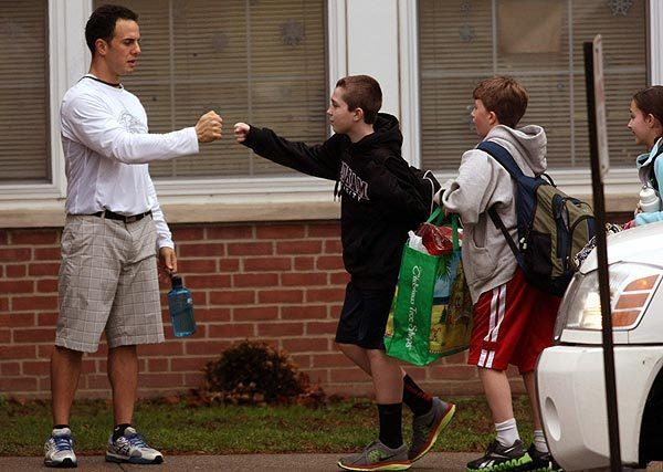 A member of Newtown Middle School faculty greets a student with a fist bump as classes resume in Newtown, Conn., on December 18, 2012.