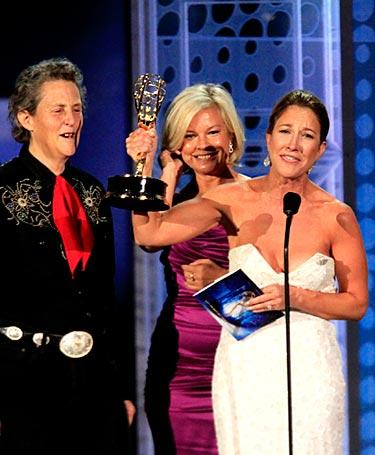 "Temple Grandin, left, takes the stage with producers Emily Gerson Saines and Alison Owen as they accept the win for made-for-television movie. The biopic ""Temple Grandin"" shares the story of Grandin's life as an autistic scientist."