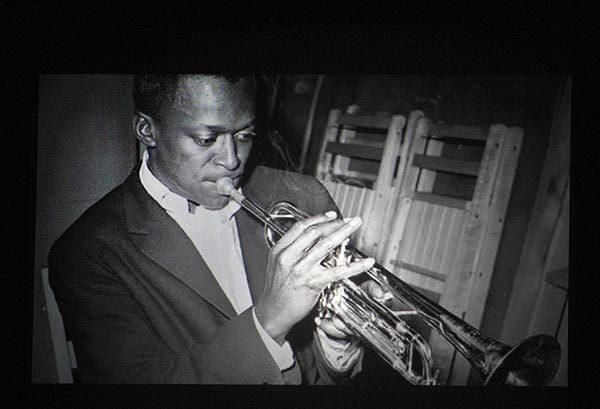 An image of Miles Davis is projected during a short video on his music shown during the concert.