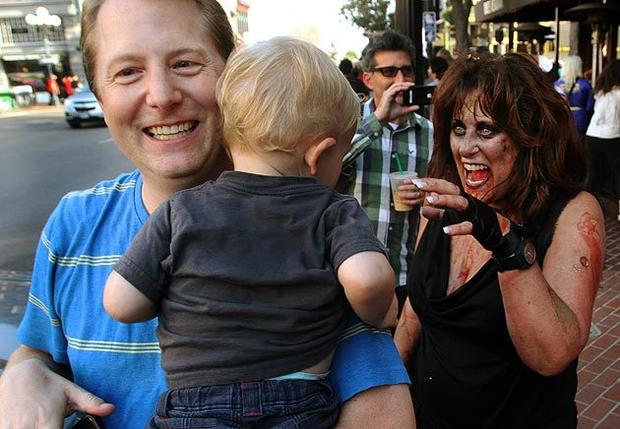 Zombie Denise James growls playfully at a child in his arms during the annual Zombie Walk: San Diego on Friday (Friday the 13th, this year), in which the would-be undead dress the part and put on their best rotting zombie faces before marching through the city's Gaslamp District.