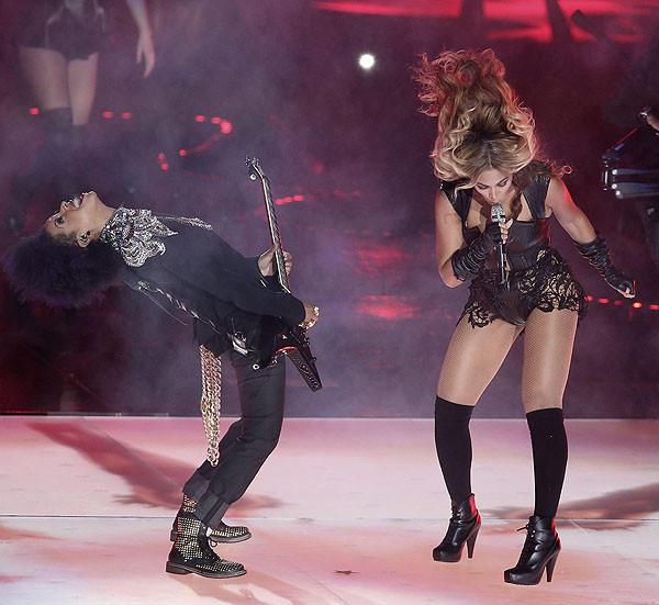 Beyonce performs with her guitarist.