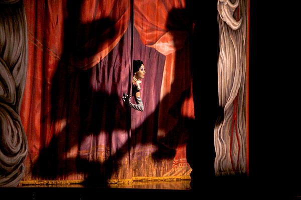 "A performer peeks through the curtain as ""Iris,"" a show about Hollywood by Cirque du Soleil, began a long run at the Kodak Theatre."